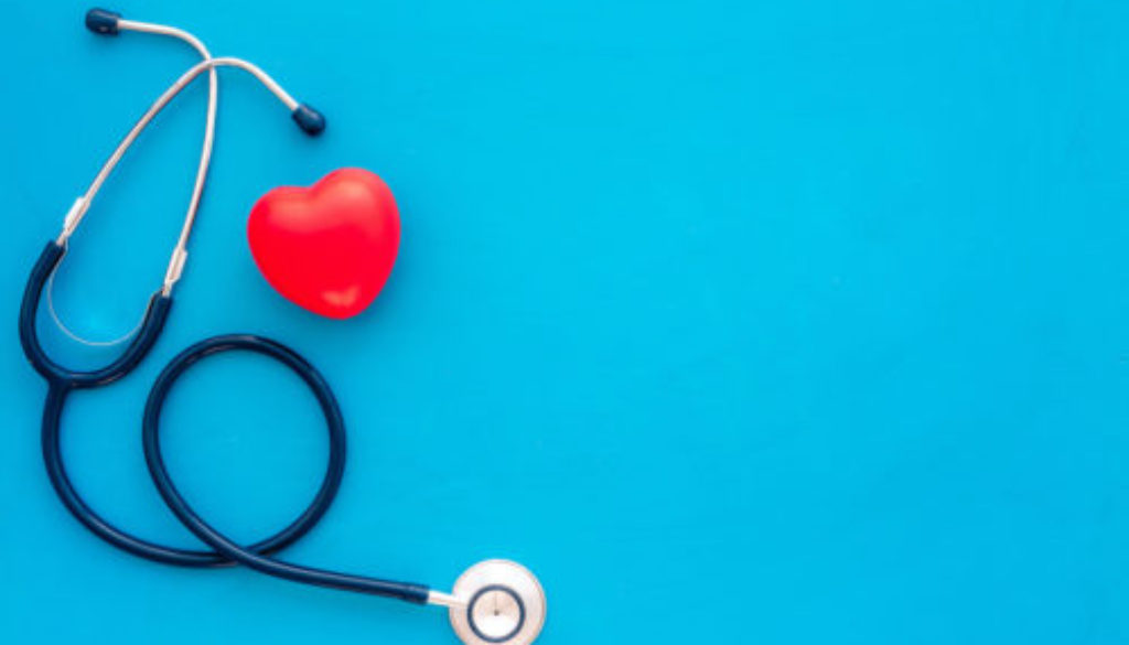 Heart health, health care concept. Stethoscope near rubber heart on blue background top view space for text